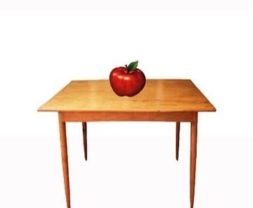 La manzana está encima de la mesa.